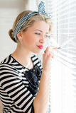 Beautiful blond pinup woman looking thoughtfully through jalousie windows Royalty Free Stock Image