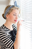 Beautiful blond pinup woman looking thoughtfully through jalousie windows Royalty Free Stock Photo