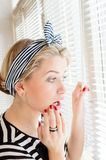 Beautiful blond pinup woman looking thoughtfully through jalousie windows Royalty Free Stock Photography
