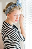 Beautiful blond pinup woman looking thoughtfully through jalousie windows Stock Image