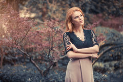 Beautiful Blond Red-haired woman girl model posing walks in park. Royalty Free Stock Photography