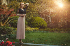 Beautiful Blond Red-haired woman girl model walks in park sunset. Stock Photos