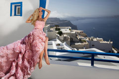 Beautiful blond runaway bride in white wedding dress fabulous with a very long train of crystals in the street on Santorini. In Greece Royalty Free Stock Photo