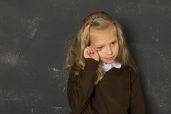 Beautiful blond schoolgirl crying sad moody and tired in front of school class blackboard Stock Photography