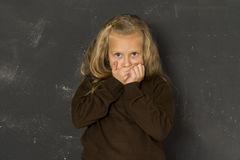 Beautiful blond schoolgirl sad moody and tired in front of school class blackboard Royalty Free Stock Photos