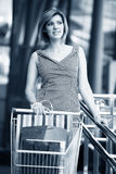 Beautiful blond with shopping cart Royalty Free Stock Photo