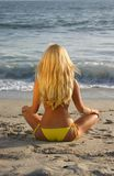 Beautiful Blond sitting on the beach Stock Photo