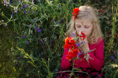 Beautiful blond smelling flowers Stock Photography