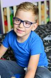 Happy with glasses. Beautiful blond smiling little boy with reading glasses without teeth posing at the camera sitting at home royalty free stock photo