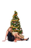 Beautiful blond smiling woman and Christmas tree. Royalty Free Stock Photography