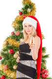 Beautiful blond smiling woman and Christmas tree. Royalty Free Stock Images
