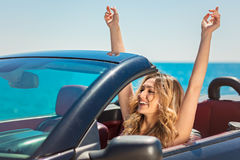Beautiful blond smiling young woman in convertible top automobile looking sideways while parked near ocean waterfront Stock Photo