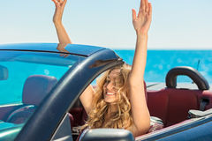 Beautiful blond smiling young woman in convertible top automobile looking sideways while parked near ocean waterfront Royalty Free Stock Photos