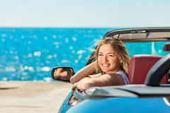 Beautiful blond smiling young woman in convertible top automobile looking sideways while parked near ocean waterfront.  Royalty Free Stock Images