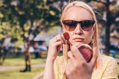 Beautiful blond in sun glasses woman corrects make-up in the street. Fashin concept royalty free stock photography