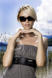 Beautiful blond in sunglasses at the lake Royalty Free Stock Photos
