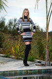 Beautiful blond in a sweater dress. Full length of a beautiful young woman posing next to a pool. She is wearing a short striped sweater dress and black stiletto Stock Photography