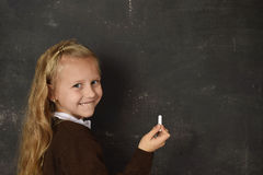 Beautiful blond sweet schoolgirl in uniform holding chalk writing on blackboard smiling happy. Young beautiful blond sweet schoolgirl in uniform holding chalk Royalty Free Stock Photos