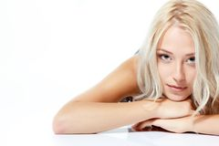 Beautiful blond teen girl lying and looking at camera. Isolated Royalty Free Stock Photography
