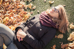 Beautiful blond teenage girl laying in autumnal park Royalty Free Stock Photography