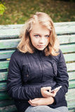 Beautiful blond teenage girl with phone in hand Stock Photo