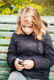 Beautiful blond teenage girl with smartphone Royalty Free Stock Photos