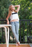 Beautiful blond teenage girl stands on balcony Stock Images