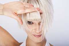 Beautiful blond with a trendy hairstyle. Beautiful blond woman with a trendy hairstyle peering out from underneath her fringe with one eye Stock Images
