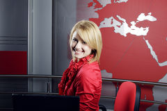 Beautiful blond TV journalist and manager. Beautiful blond Television journalist in front of the laptop looking at the camera Royalty Free Stock Image