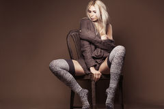 Beautiful blond wearing cardigan and stockings on the chair Royalty Free Stock Photos