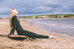 Beautiful blond in wet suit with surfboard at beach Stock Photos