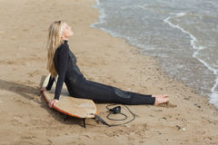 Beautiful blond in wet suit with surfboard at beach Royalty Free Stock Photos