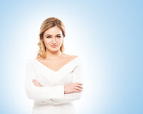 Beautiful blond in white knitwear on blue background Royalty Free Stock Image