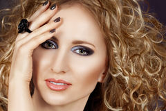 Beautiful blond woman. With long curly hair and smoky eyeshadow wearing grey manicure Royalty Free Stock Photos