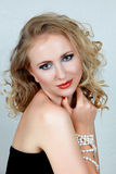 Beautiful blond woman. With curly hair and dark evening make-up wearing corset and pearls Stock Images