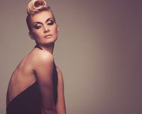 Beautiful blond woman. Fashionable woman in black with creative hairstyle Stock Photography