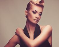 Beautiful blond woman. Fashionable woman in black with creative hairstyle Stock Photos