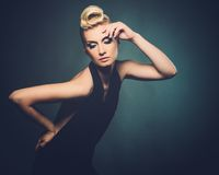 Beautiful blond woman. Fashionable woman in black with creative hairstyle Royalty Free Stock Image