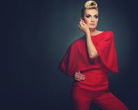 Beautiful blond woman. Fashionable woman in red with creative hairstyle Stock Image