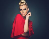 Beautiful blond woman. Fashionable woman in red with creative hairstyle Stock Photography