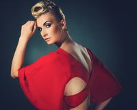 Beautiful blond woman. Fashionable woman in red with creative hairstyle Stock Images