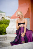 Beautiful blond woman. In purple dress sat on steps outdoors Royalty Free Stock Photos