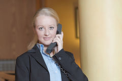 Beautiful blond woman answering a telephone Royalty Free Stock Images