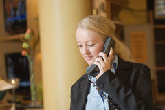 Beautiful blond woman answering a telephone Royalty Free Stock Photos