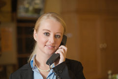 Beautiful blond woman answering a telephone Stock Photo