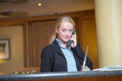 Beautiful blond woman answering a telephone Royalty Free Stock Photography