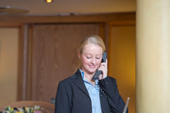 Beautiful blond woman answering a telephone Stock Photos