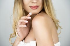 Beautiful blond woman applying beauty cream on her shoulder close up isolated white background royalty free stock photos