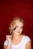 Beautiful blond woman applying eye makeup Stock Image