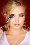 Beautiful blond woman applying eye makeup Stock Photos